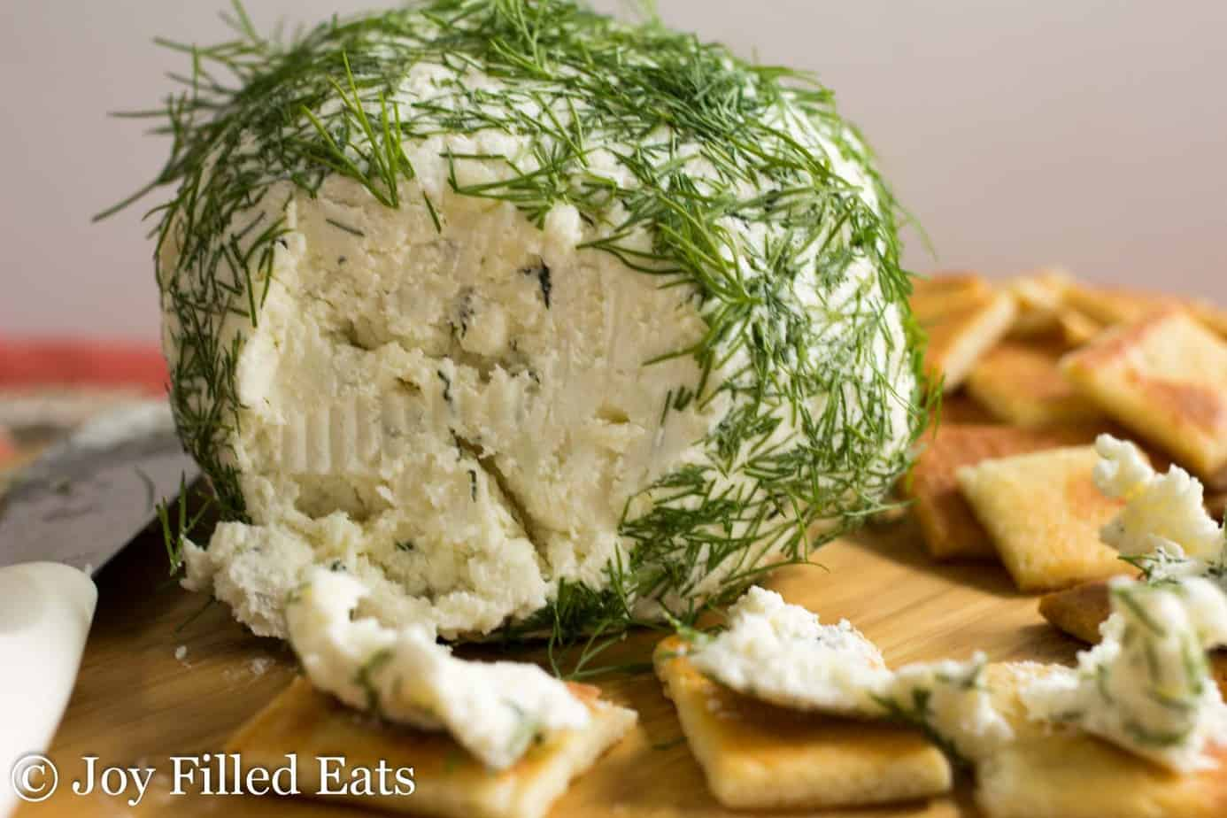 large ball of feta and dill cheese set on a cutting board surrounded by crackers with portion of cheese ball removed