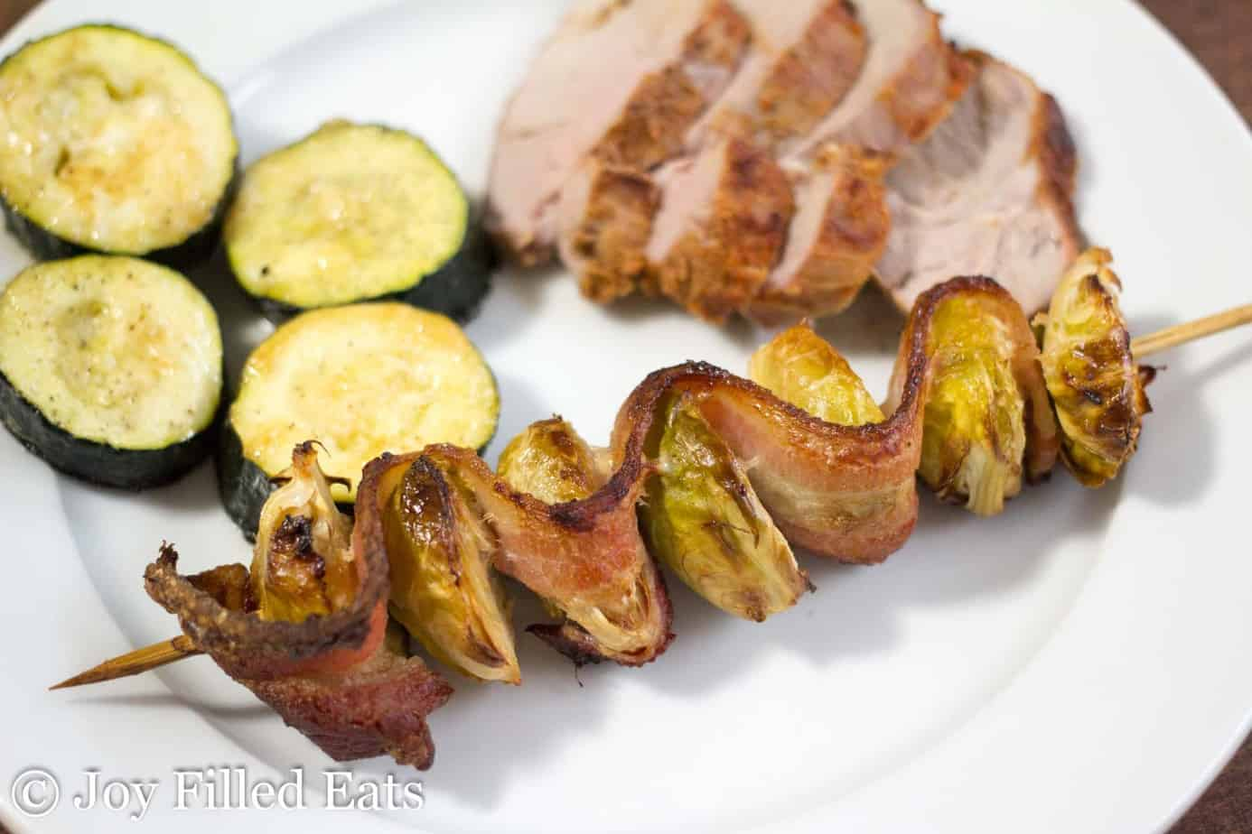 bacon & Brussels sprout kebab resting on a white plate with a side of zucchini and sliced pork