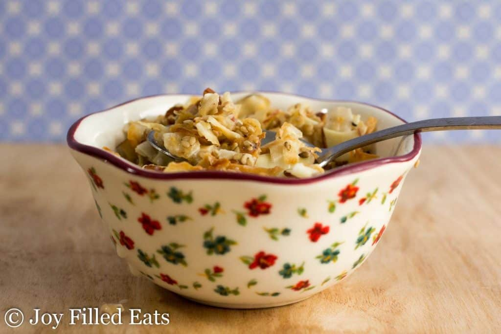 decorative bowl of almond coconut sesame seed granola with spoon resting on the rim