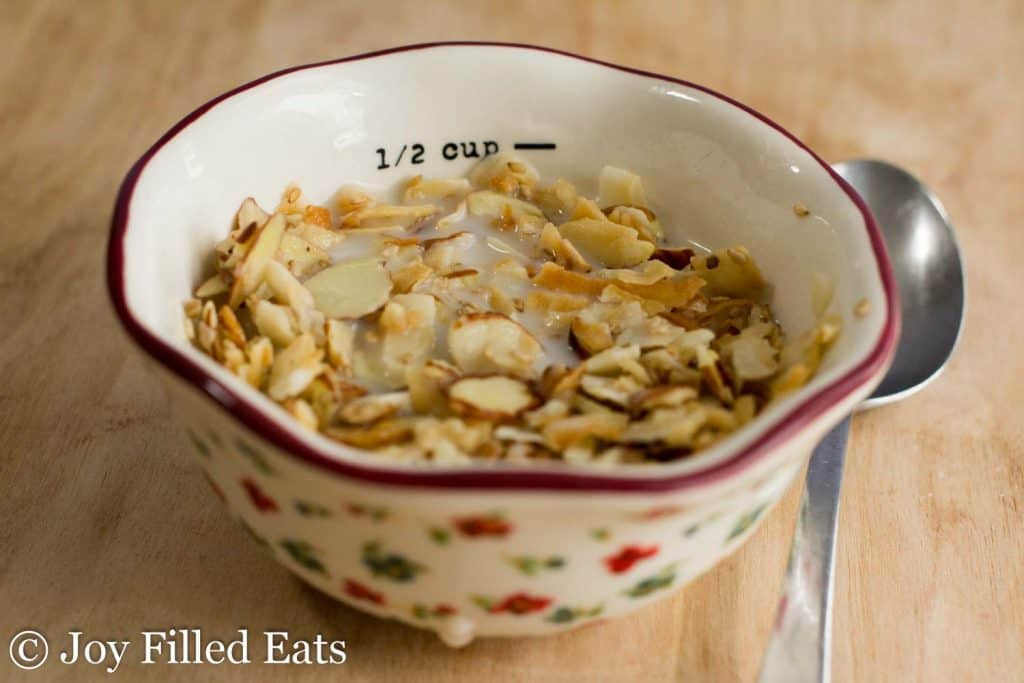 decorative bowl full of almond coconut sesame seed granola set next to a spoon