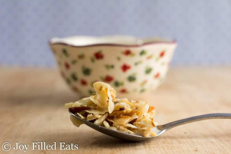 spoon full of almond coconut sesame seed granola set in front of decorative bowl