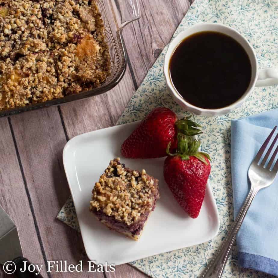 overhead view of white plate with slice of blackberry coffee cake and strawberries set next to a cup of coffee and baking dish full of more coffee cake