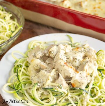 mozzarella & pesto chicken casserole topped on zucchini noodles on a plate set net to a platter of more zucchini noodles and casserole dish