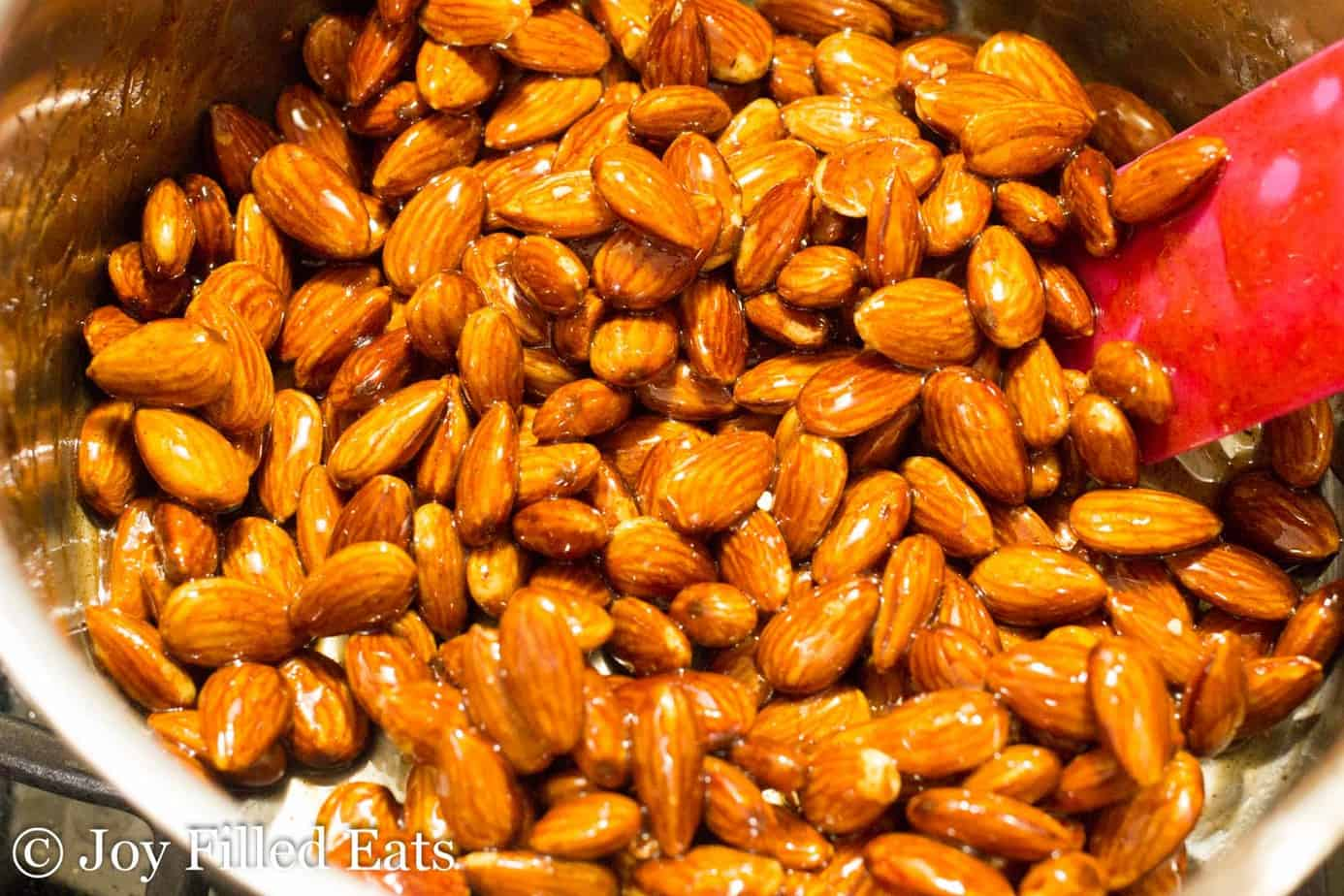glazed almonds in a sauce pan up close