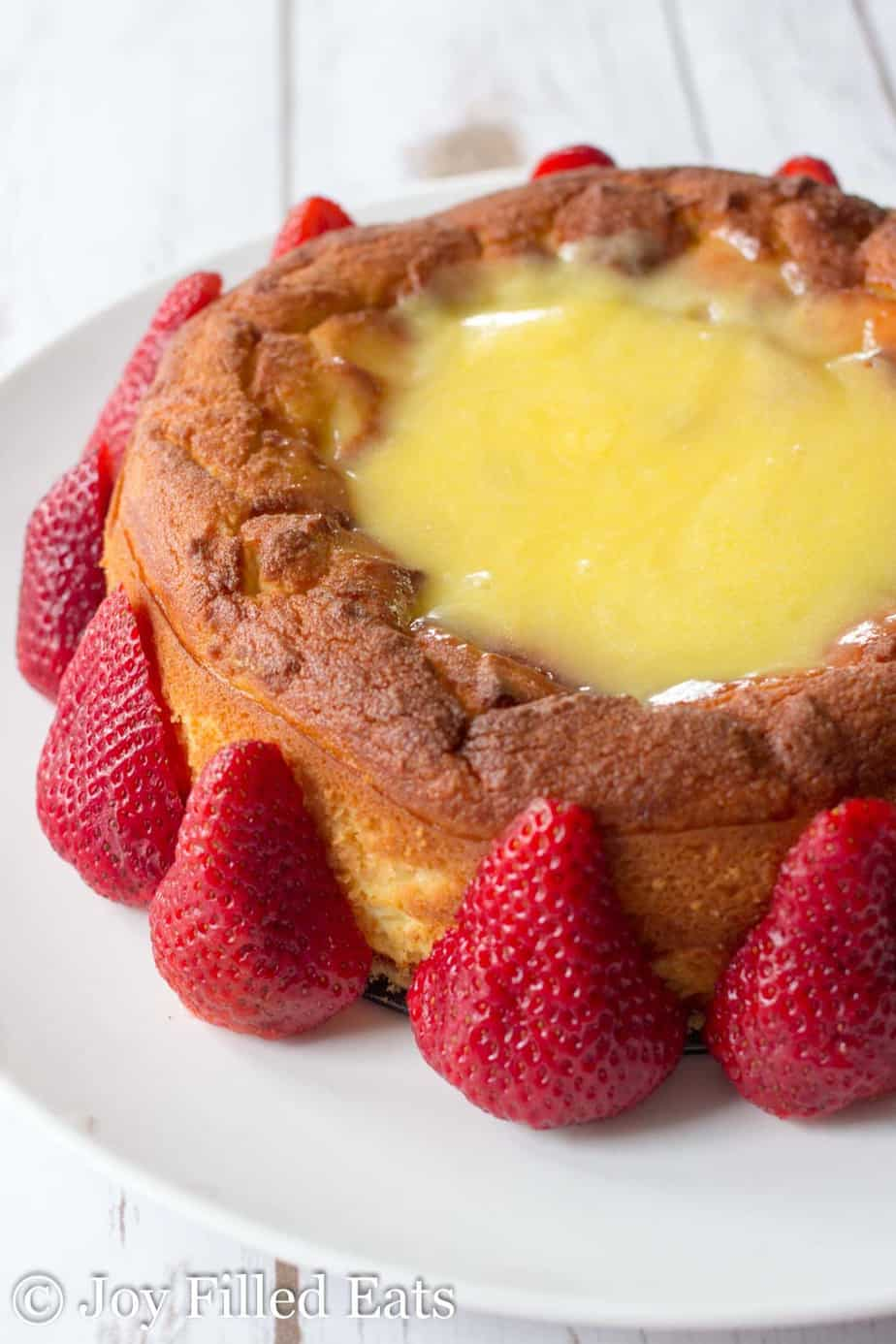 My Triple Layer Lemon Curd Cake on a white plate rimmed with strawberries
