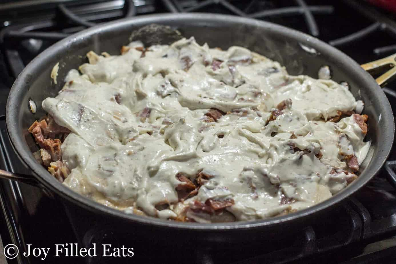 close up on chicken cordon bleu cooking on the stove top in a skillet