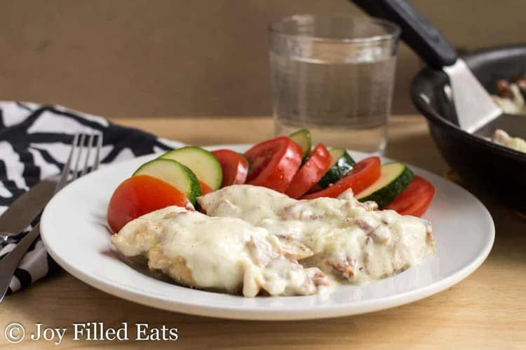 chicken cordon bleu on a white plate next to fanned out sliced vegetables