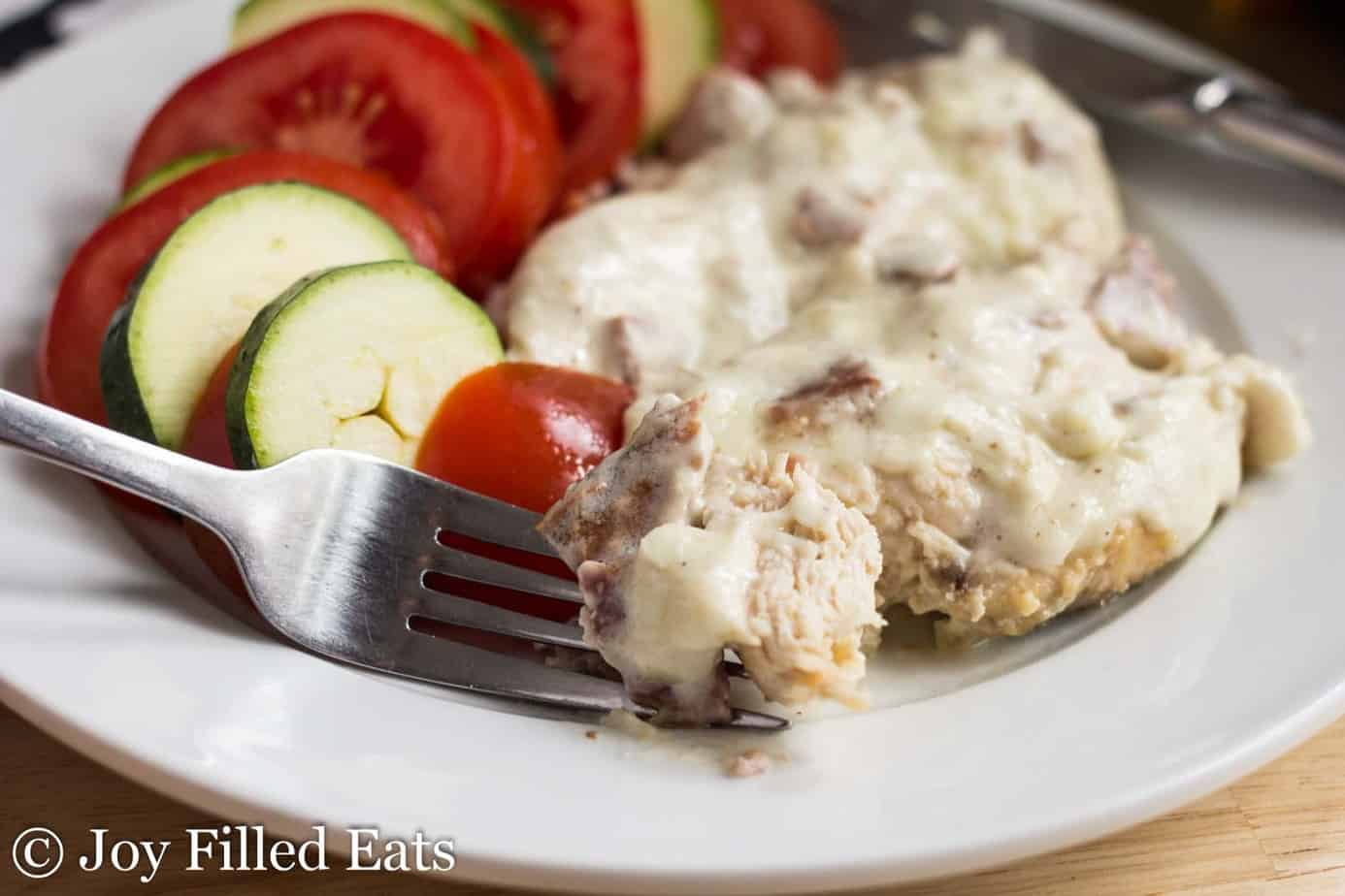 bite of chicken cordon bleu on a fork laying on a plate with a serving of chicken cordon bleu and sliced vegetables