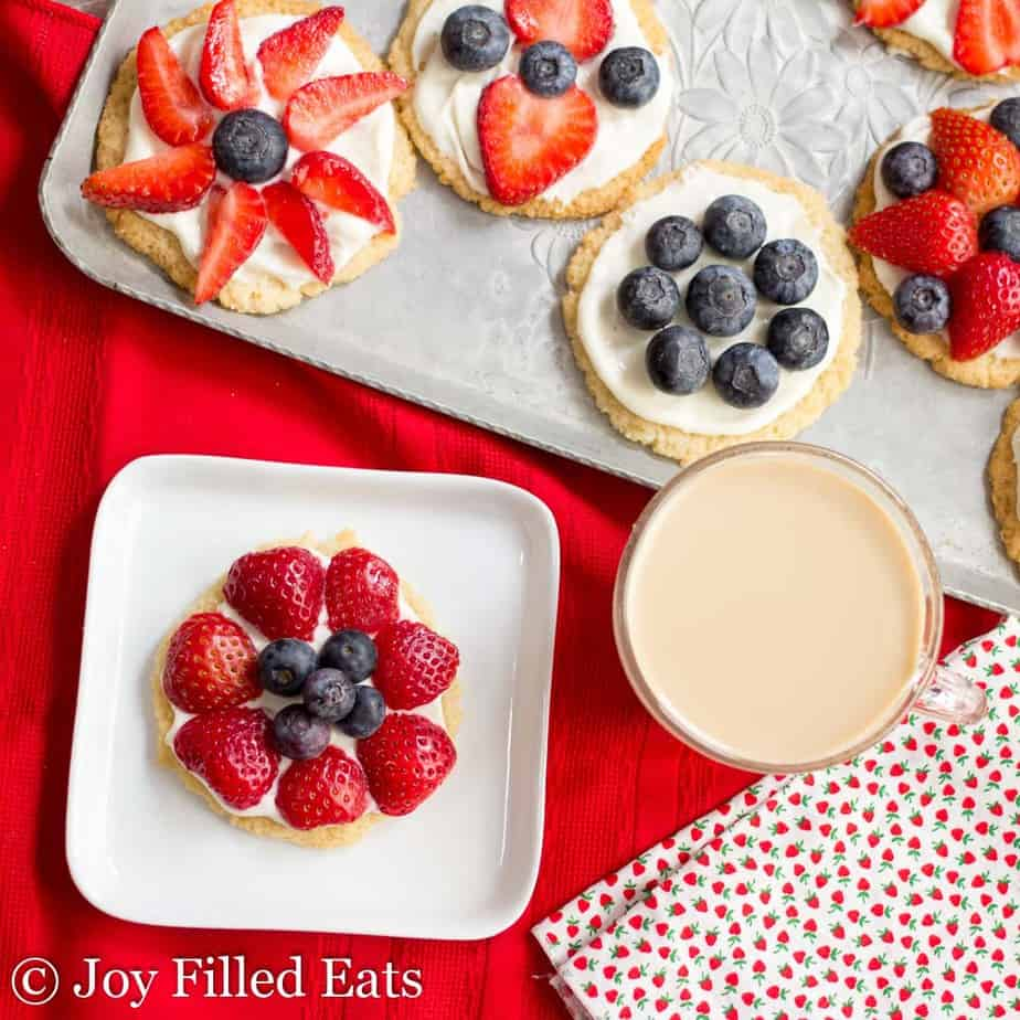 An assortment of berry topped healthy fruit pizza cookies on a metal tray and white square plate