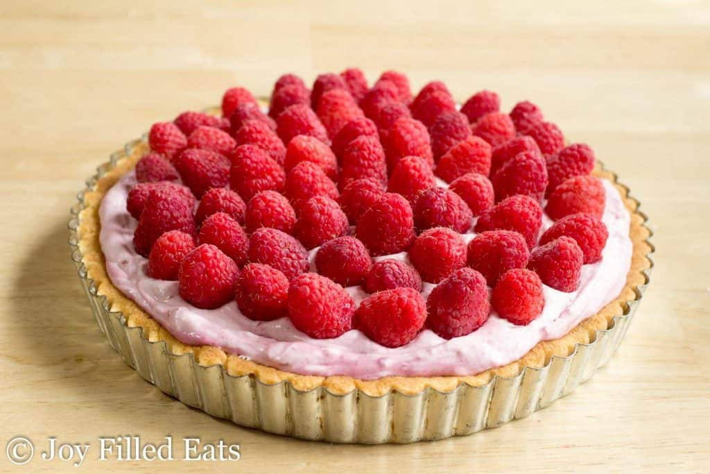 raspberry mousse tart in a pie plate topped with fresh raspberries