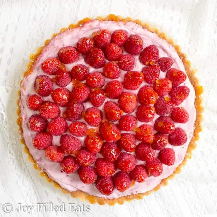 overhead view of raspberry mousse tart topped with fresh raspberries