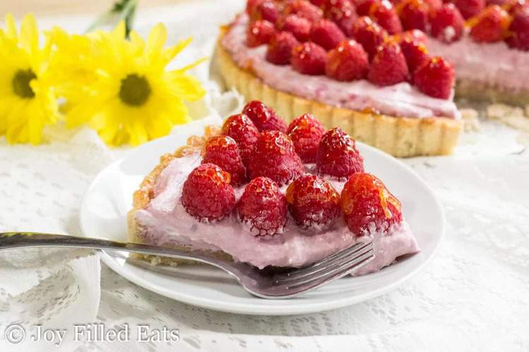 slice of raspberry mousse tart on a plate with a fork