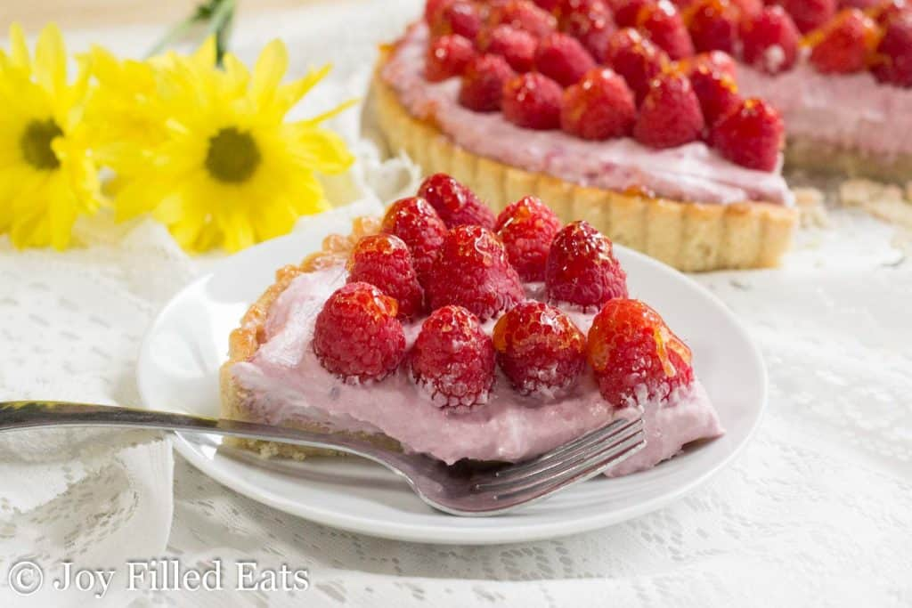 slice of raspberry mousse tart on a plate with fork next to remaining tart