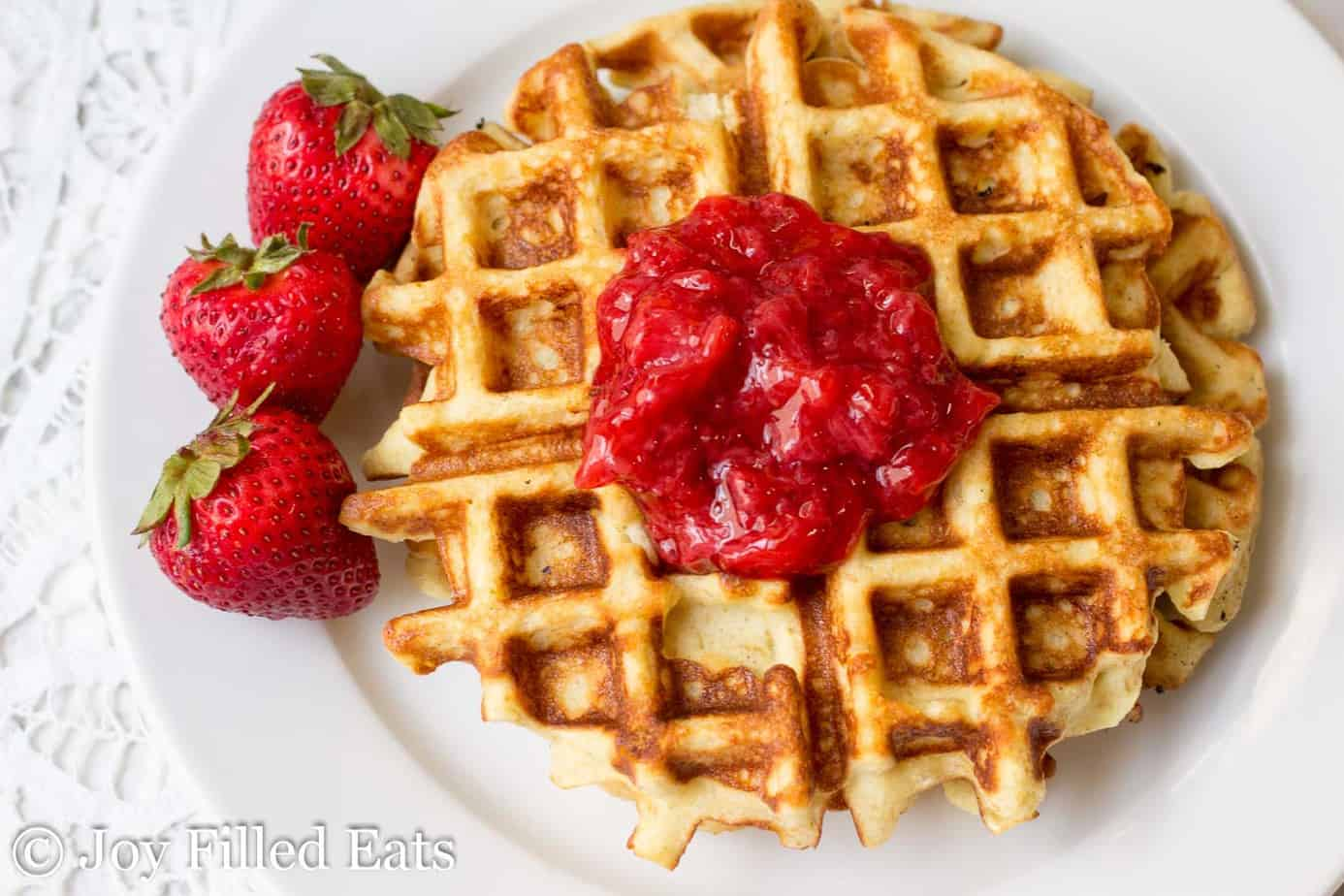 almond flour vanilla waffles topped with strawberry jam and served next to whole strawberries