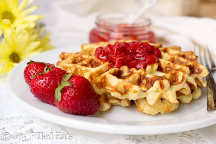 stack of vanilla waffles with almond flour topped with strawberry jam and severed with a fork and whole strawberries