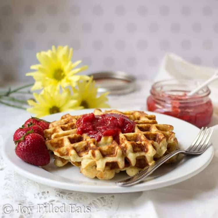 vanilla waffles on a white plate topped with jam on a plate with a fork and whole strawberries