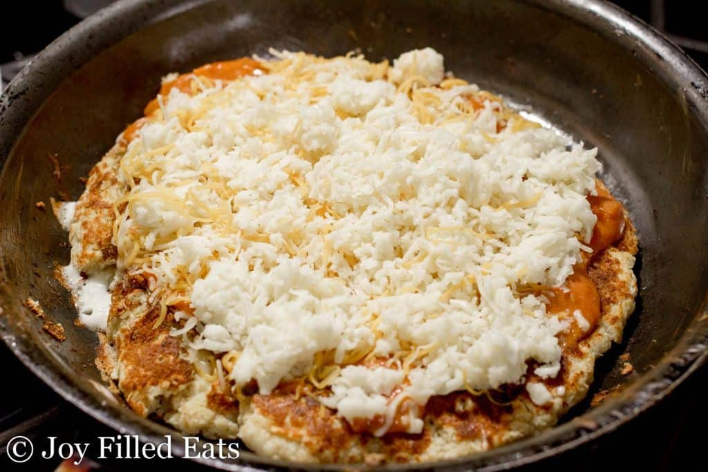 low carb pizza cooking in skillet and topped with grated cheese