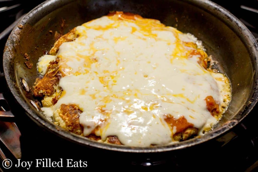 low carb skillet pizza cooking and covered in melted cheese