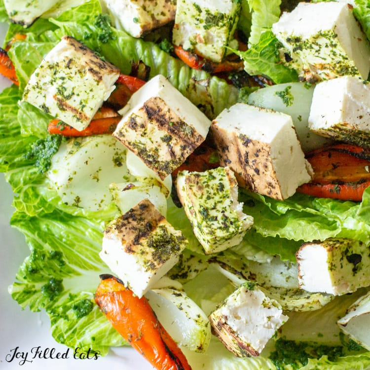 close up of grilled paneer on top of a green salad