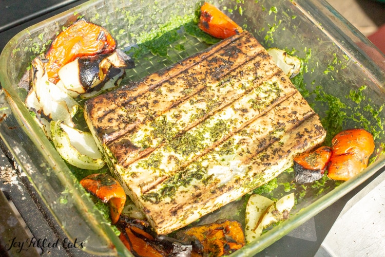 The grilled cheese and vegetables in a glass pyrex dish