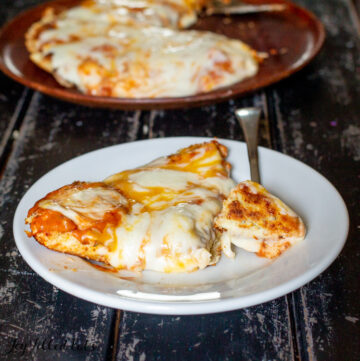 low carb skillet pizza with slice missing and serving spatula next to fork and plate with slice of pizza