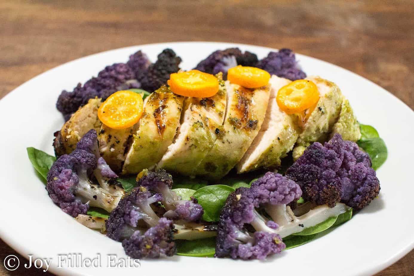 citrus basil grilled chicken topped with halved yellow cherry tomatoes onto a bed of spinach surrounded by purple cauliflower