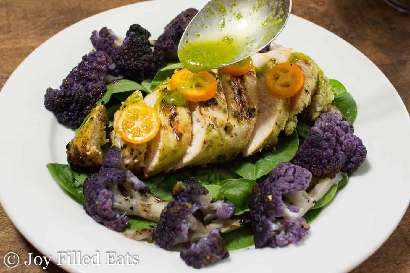 spoon pouring citrus basil dressing onto grilled chicken atop of a bed of spinach surrounded by purple cauliflower