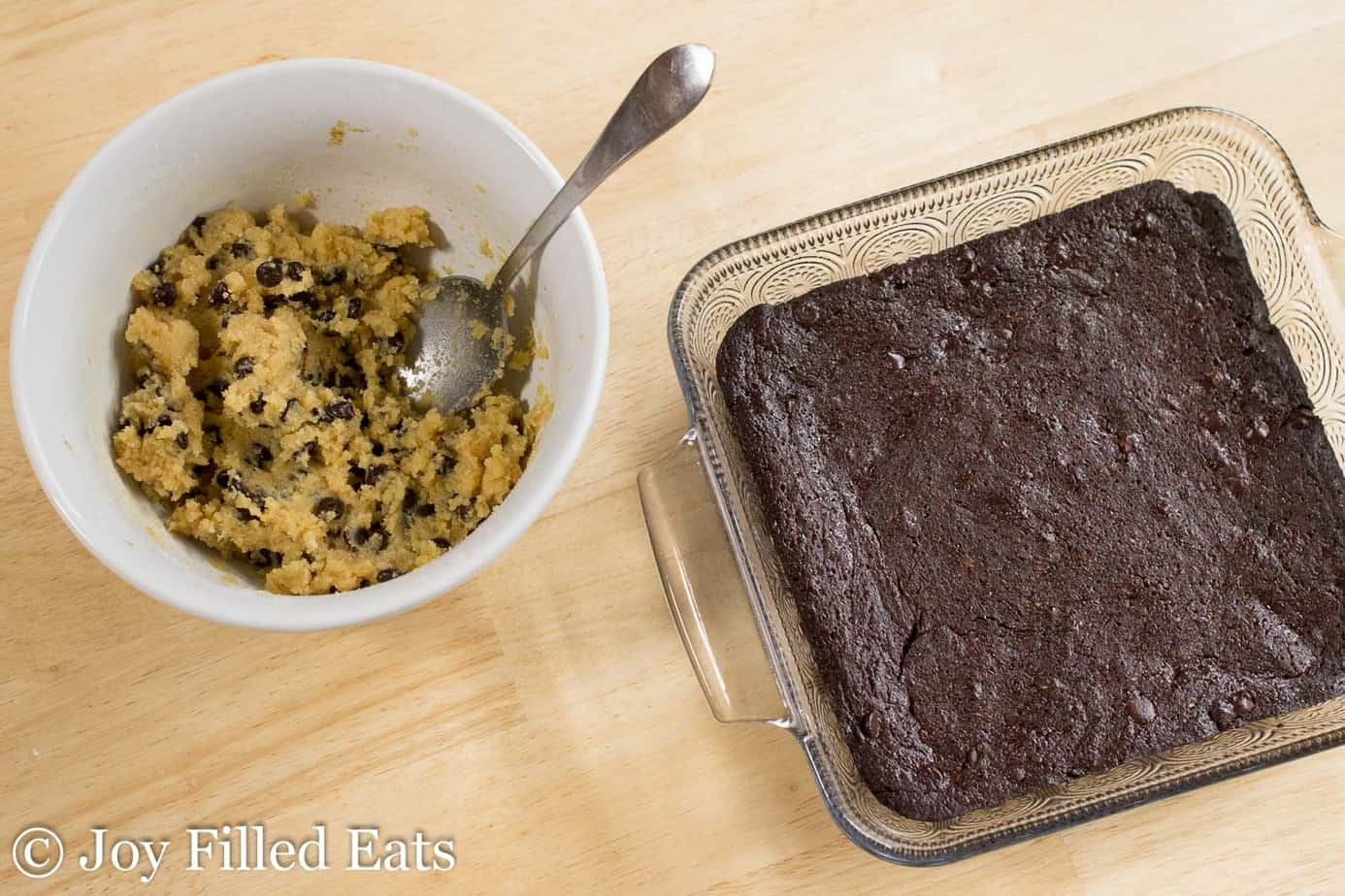 baking dish filled with brownies next to a bowl of chocolate chip cookie dough