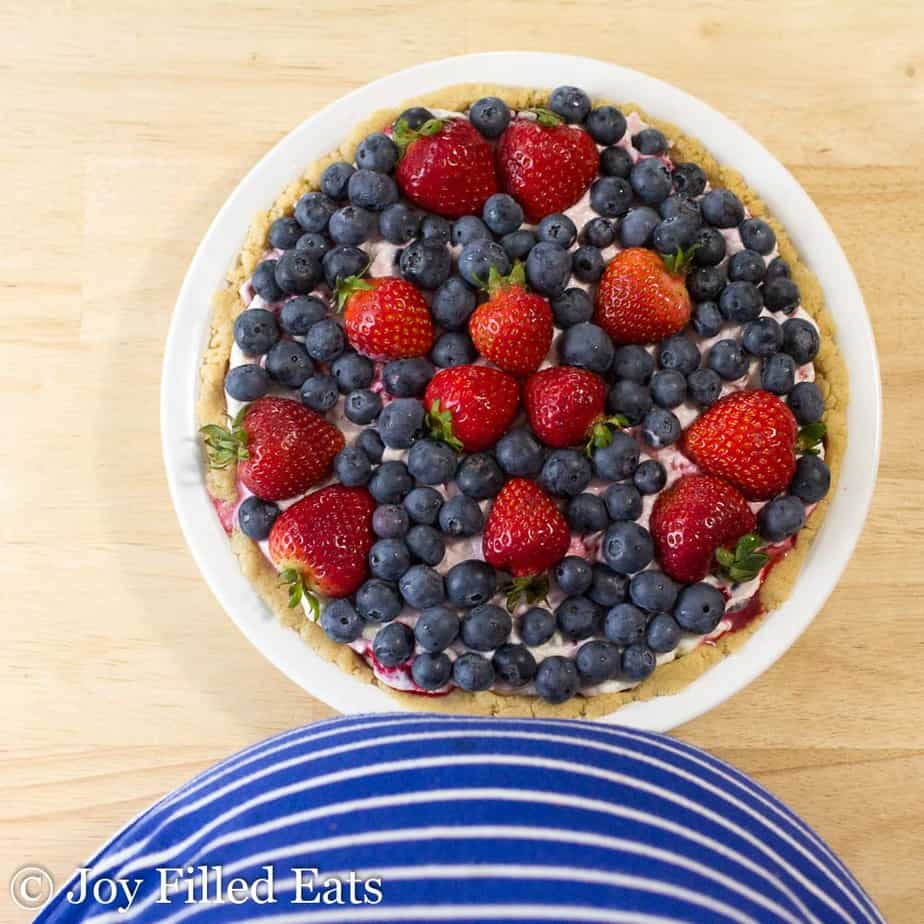 overhead view of no bake berry cheesecake topped with blueberries and strawberries