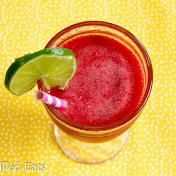 overhead view of sparkling raspberry lime soda with a lime slice on the rim with paper straw