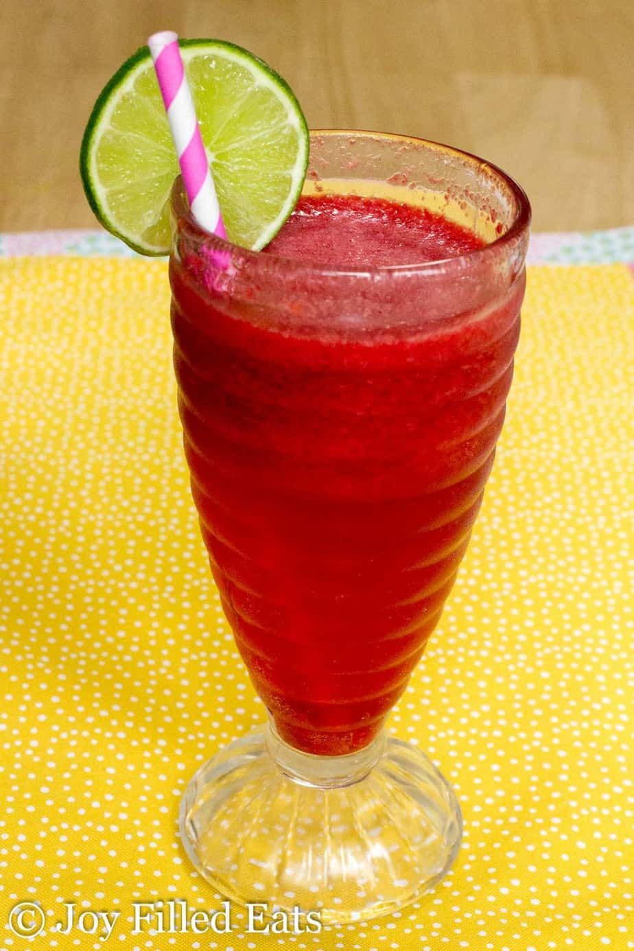 sparkling raspberry lime soda in a tall glass with a lime slice on the rim and paper straw