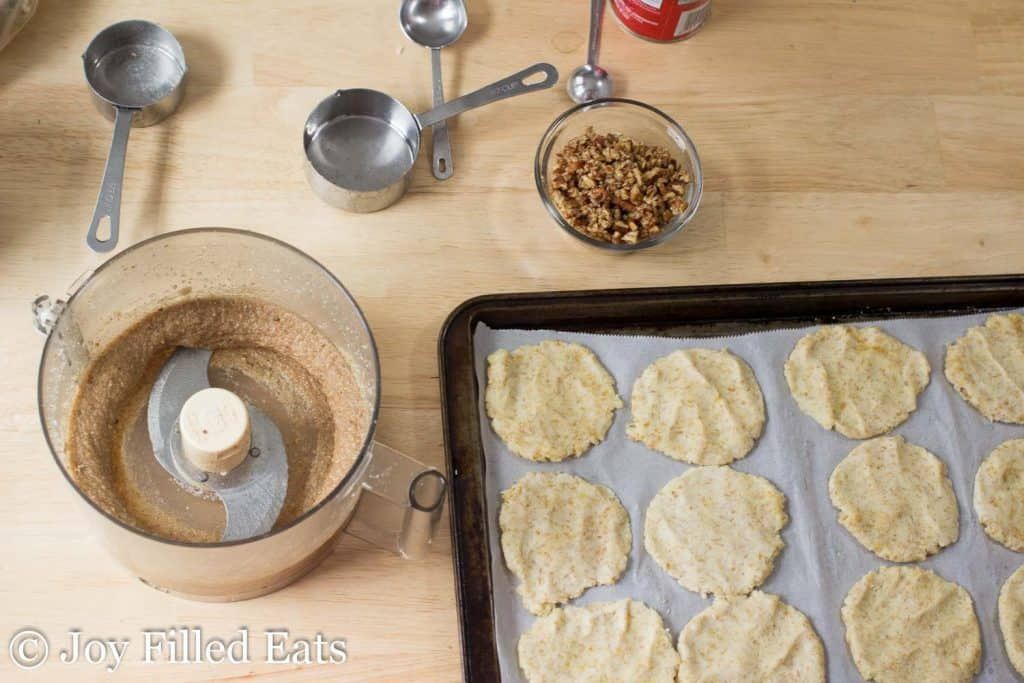 sheet pan lined with danish dough circles next to a food processor filled with Pecan filling