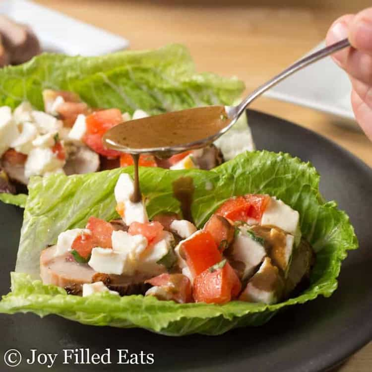 hand using spoon to pour balsamic dressing onto pork tenderloin caprese salad lettuce wrap