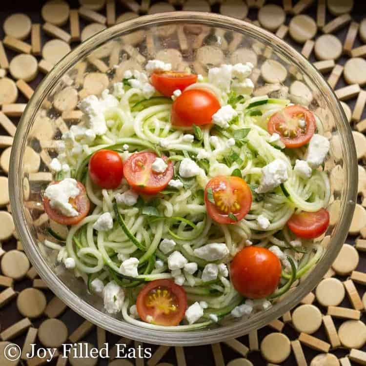 Zucchini salad with feta and tomatoes in a glass bowl