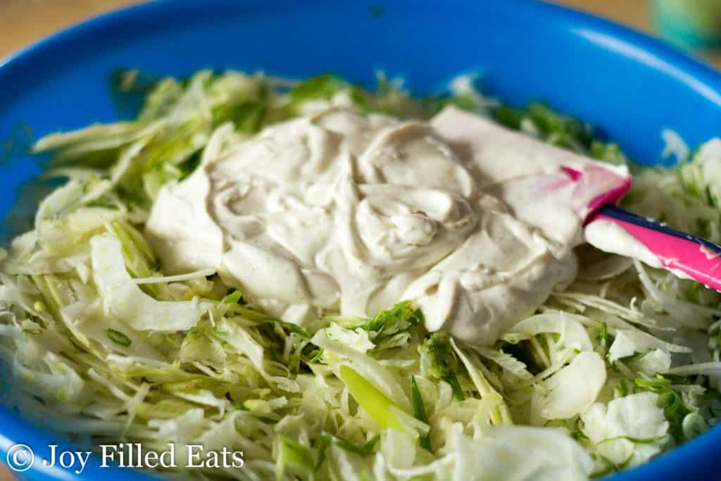 dressing for the easy coleslaw with fennel on top of the shredded cabbage in a large bowl