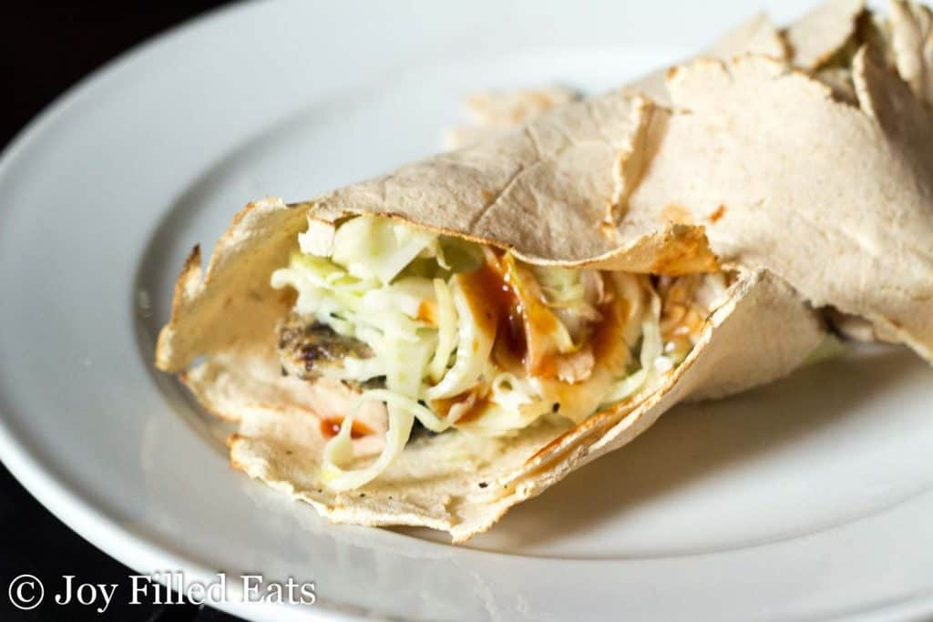 wrap sandwich containing coleslaw with fennel on a white plate