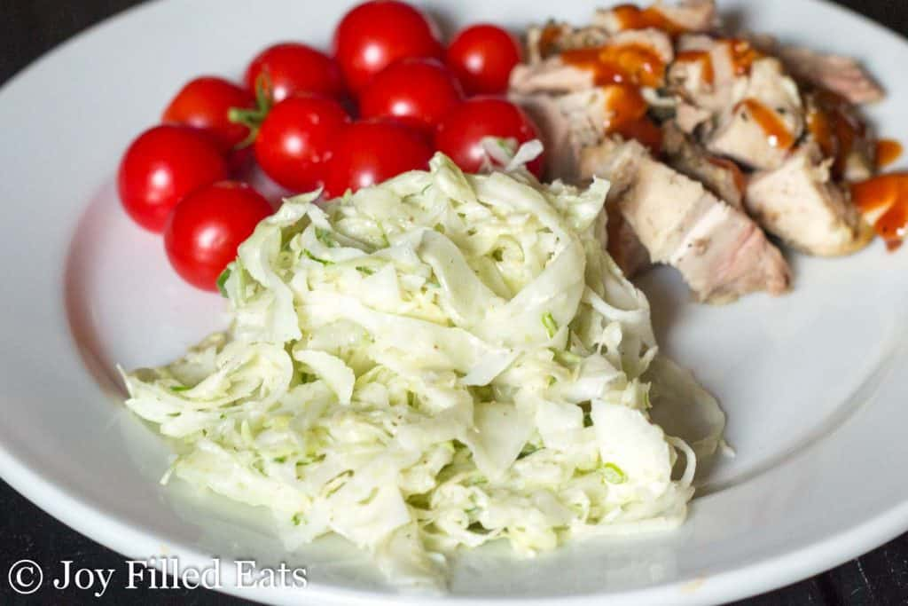 a scoop of easy coleslaw with fennel on a plate with bbq chicken and tomatoes
