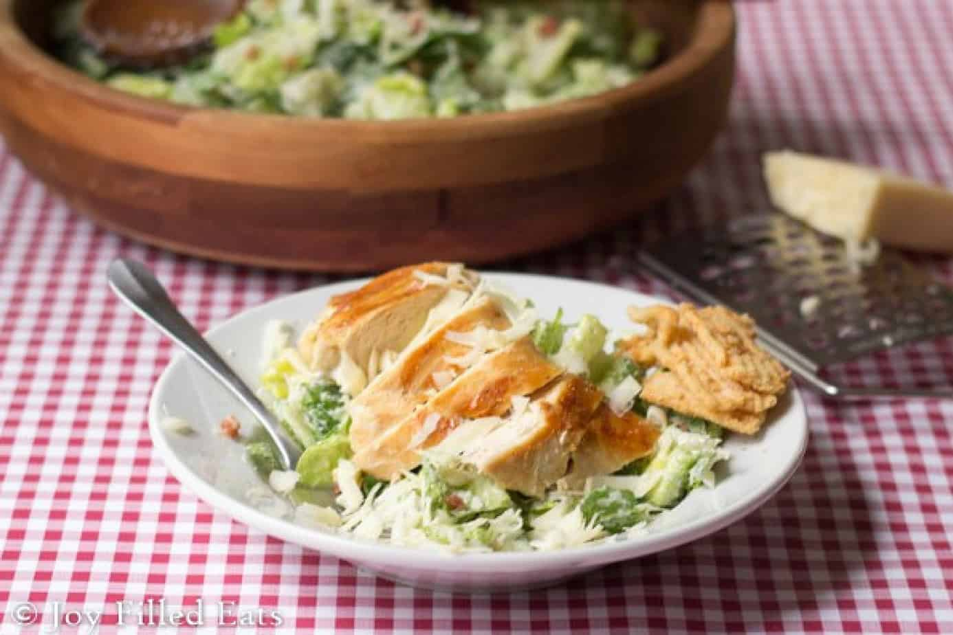easy Caesar salad topped with grilled chicken and two minute dressing on a white plate