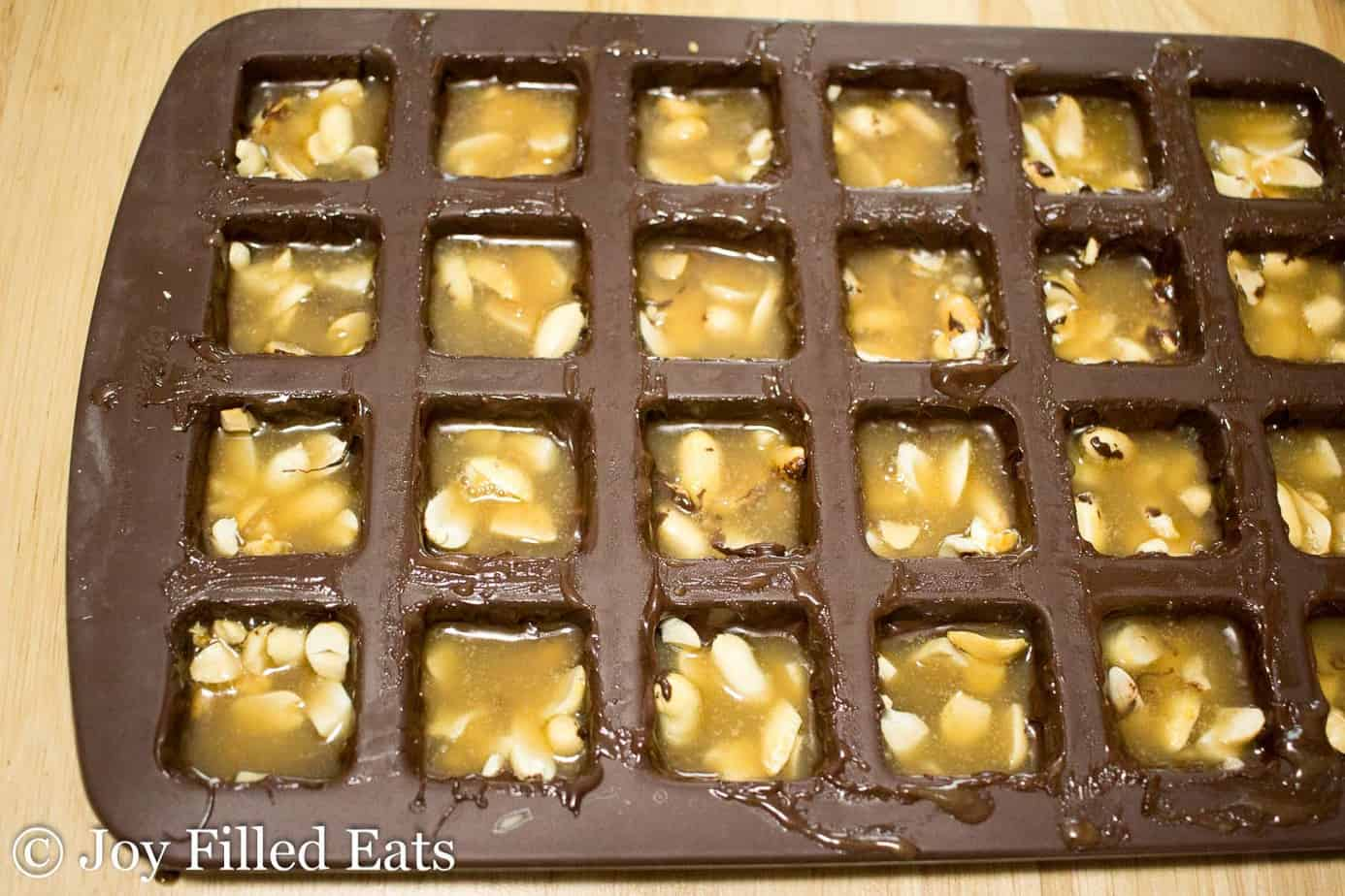 caramel poured into molds on tray for mini snickers ice cream bars