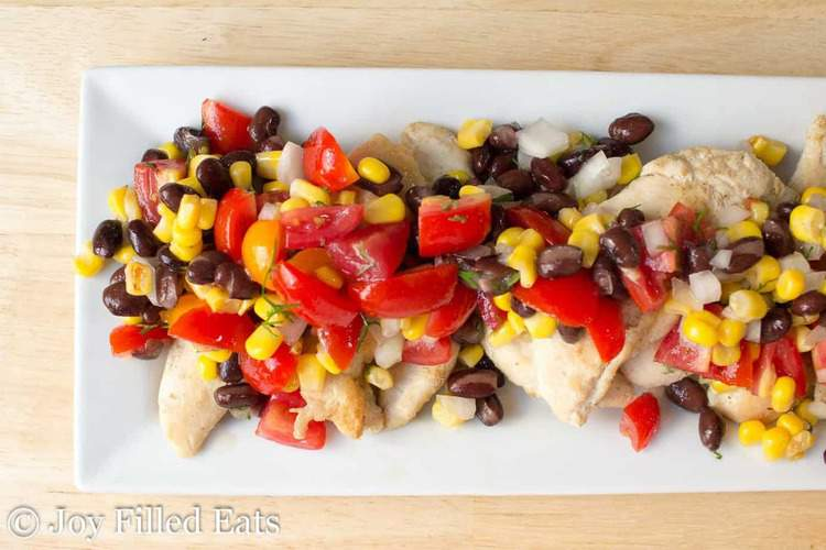 overhead view of cumin rubbed chicken topped with black bean & corn salsa on a white platter