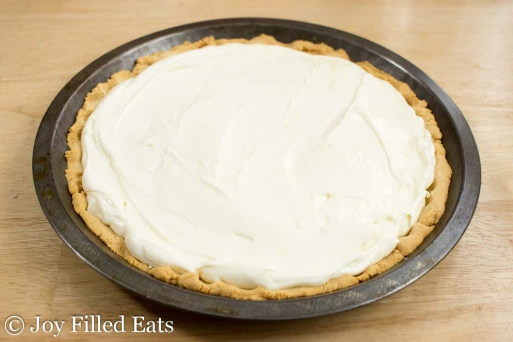 The low carb pie crust in a tin pie plate topped with the ricotta pie filling