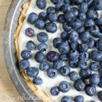 Lemon Ricotta Pie topped with fresh blueberries in a pie tin close up
