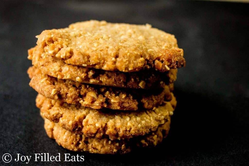 crunchy peanut cookies stacked on a black background