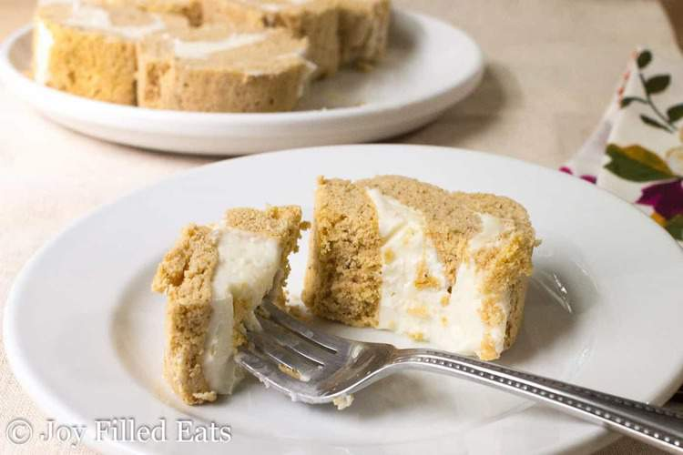 bite of mini pumpkin cake roll with cream cheese on a fork laying on a white plate with more cake