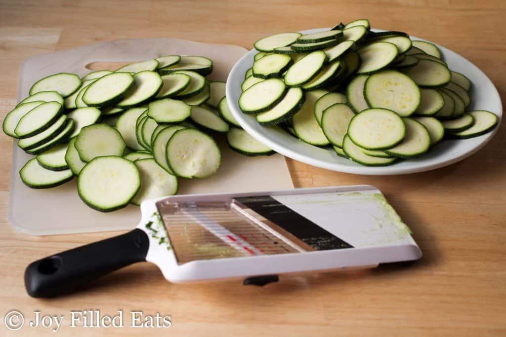 plate and cutting board full of zucchini slices next to a vegetable slicer