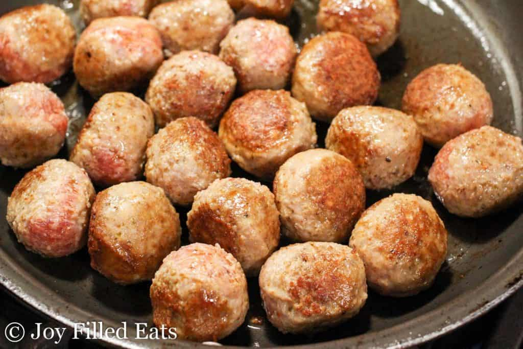 meatballs browning in a skillet