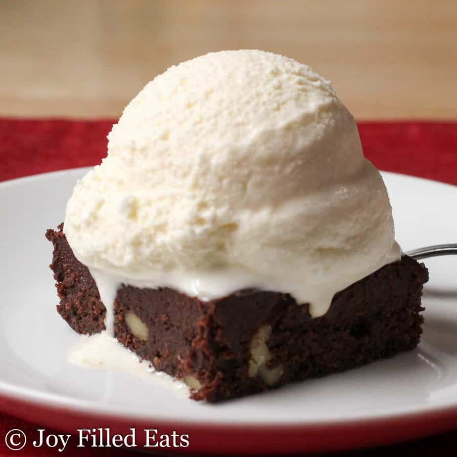 A big scoop of homemade vanilla ice cream from this keto ice cream recipe on top of a brownie on a white plate