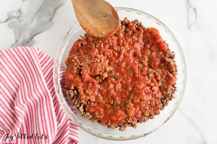 salsa and meat spread on top of cream cheese in a pie plate for the layered taco dip