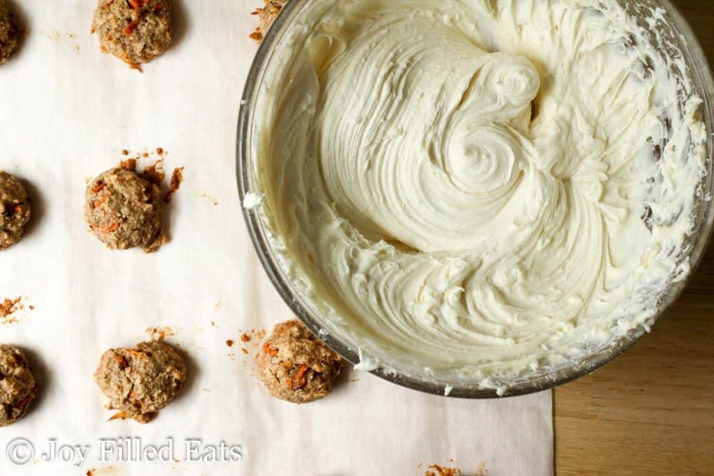 cream cheese frosting whipped in a mixing bowl next to mini carrot cake cookie bites