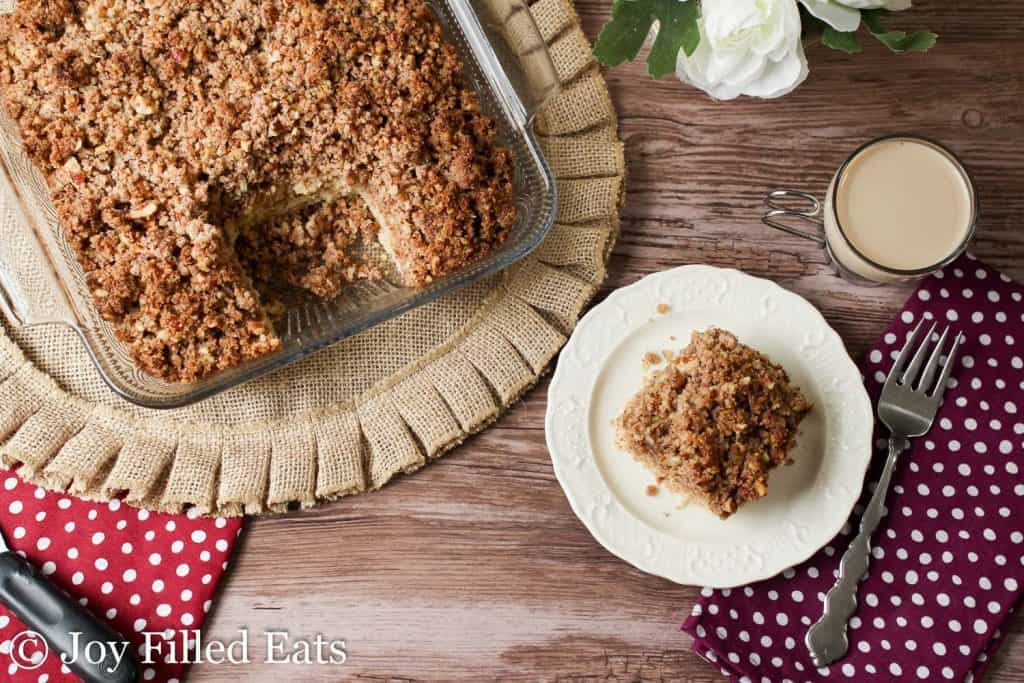 plate with slice of cinnamon pecan crumb cake next to a casserole dish filled with crumb cake